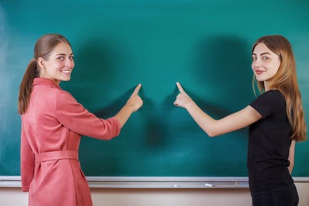 O estudante com professor está na sala de aula no quadro-negro. conceito de educação.