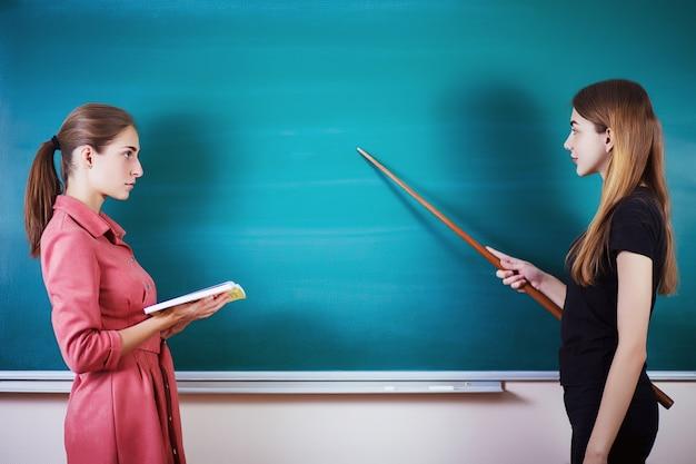 O estudante com professor está na sala de aula no quadro-negro. dia do professor.