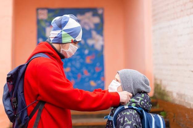 O estudante corrige máscara protetora de amigo