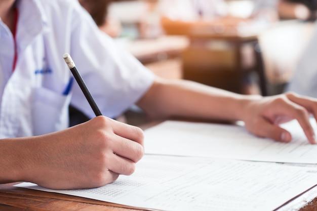O estudante da escola está tomando o exame e está escrevendo a resposta na sala de aula para o conceito do teste da educação.