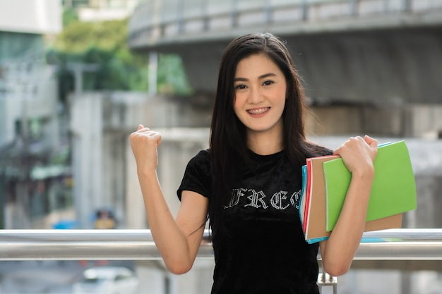 O estudante de mulher asiático levantou o punho com guardar livros.