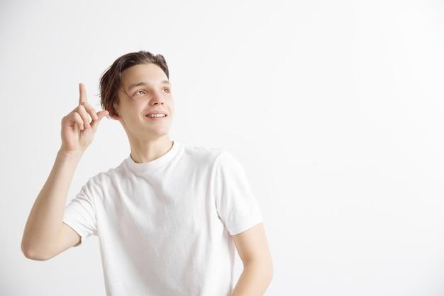O estudante feliz em pé e sorrindo contra walll cinza.