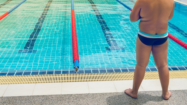 O estudante gordo do menino pronto para nadar o exercício para perde o peso para saudável.
