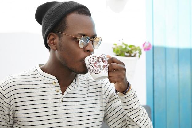 O estudante masculino afro-americano novo seguro vestiu-se à moda apreciando o café no café da faculdade. na moda, olhando o homem de pele escura com caneca bebendo chá enquanto almoça no restaurante acolhedor sozinho