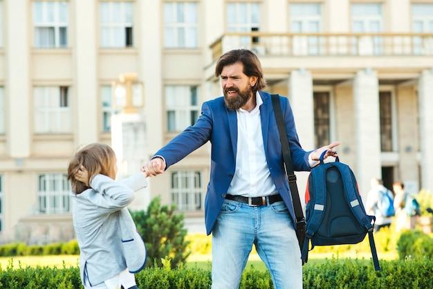 O estudante não quer ir para a escola. pai levando filho para a escola.