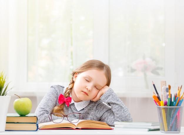 O estudante sentado à mesa adormeceu no livro.