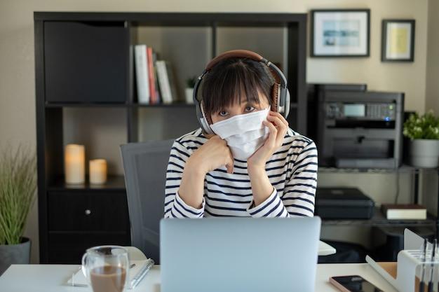O estudante universitário usa máscara e trabalha com o computador em casa. ouvindo aula on-line.