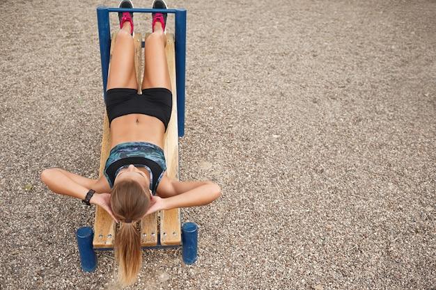 O exercício ao ar livre da mulher senta levanta