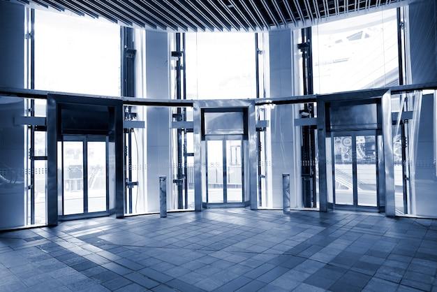 O exterior é um elevador de parede de cortina de vidro, gráfico de tom azul.