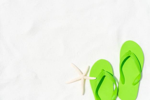 O falhanço de aleta verde pôs ou pisa sobre no fundo branco da praia arenosa com starfish.