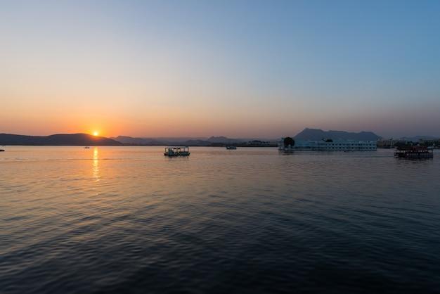 O famoso palácio branco no lago pichola ao pôr do sol.