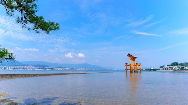 O famoso portão xintoísta japonês flutuante de laranja (torii) do santuário de itsukushima, ilha de miyajima na prefeitura de hiroshima, japão