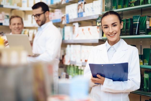 O farmacêutico fêmea prende um dobrador com papéis em uma farmácia.