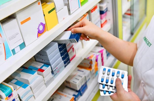 O farmacêutico que guarda a caixa e a cápsula da medicina embalam na drograria da farmácia.