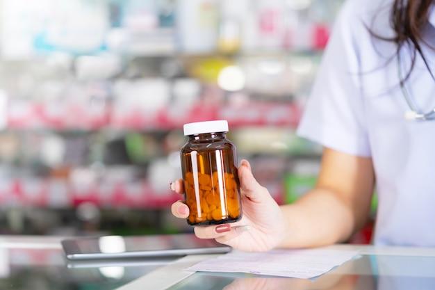 O farmacêutico segura um frasco de remédio na farmácia