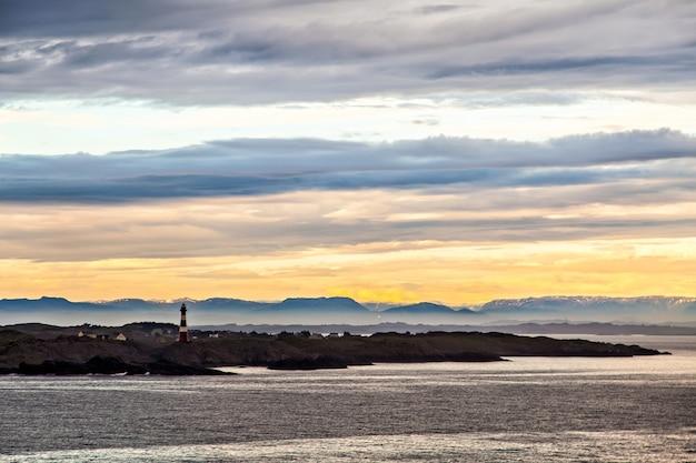 O farol e a silhueta das montanhas ao anoitecer, na noruega