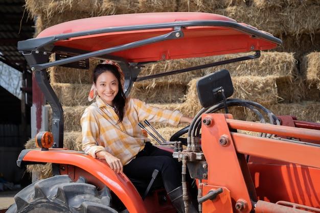 O fazendeiro, ela está com seu trator. atrás dele estava uma pilha de palha para alimentar vacas
