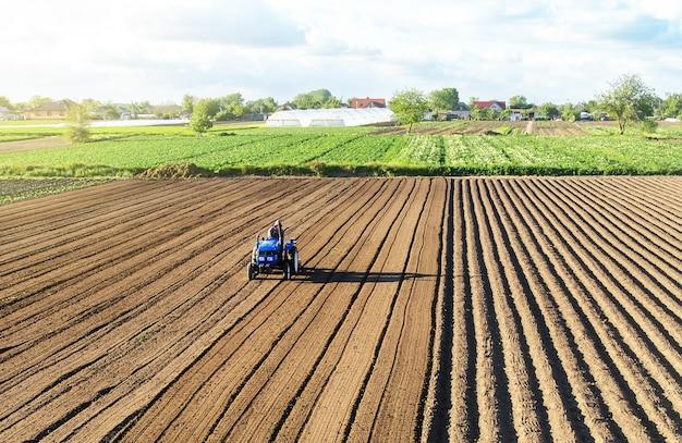 O fazendeiro em um trator cultiva a terra após a colheita.