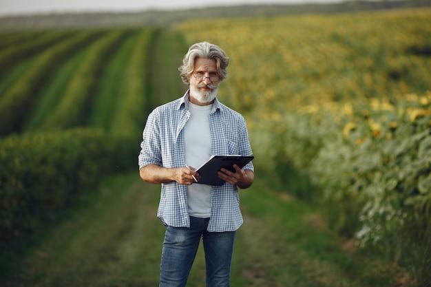 O fazendeiro examina o campo. agrônomo ou fazendeiro examina o crescimento do trigo.