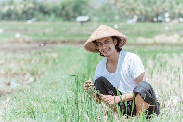 O fazendeiro sorri de chapéu enquanto se agacha nos campos de arroz