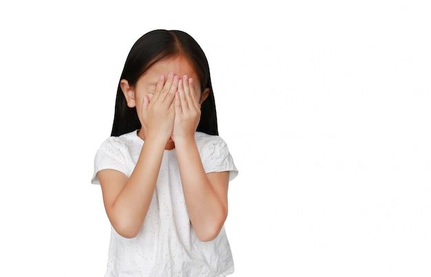 O fechamento caucasiano pequeno da menina da criança escondeu os olhos isolados à mão com espaço da cópia. kid está chorando e esfregando os olhos com as mãos.