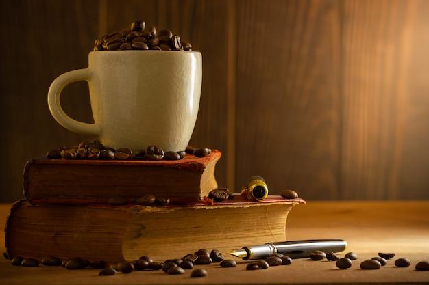 O feijão de café no copo branco e o vintage registram o empilhamento na tabela de madeira na luz da manhã.