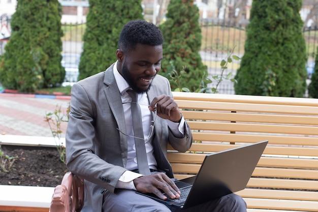 O feliz afro-americano na rua com laptop, freelancer