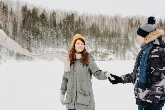 O feliz casal apaixonado no parque natural da floresta na estação fria