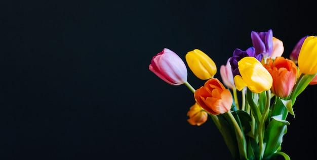 O feriado colorido floresce tulipas em um fundo preto. cartão com um espaço de cópia