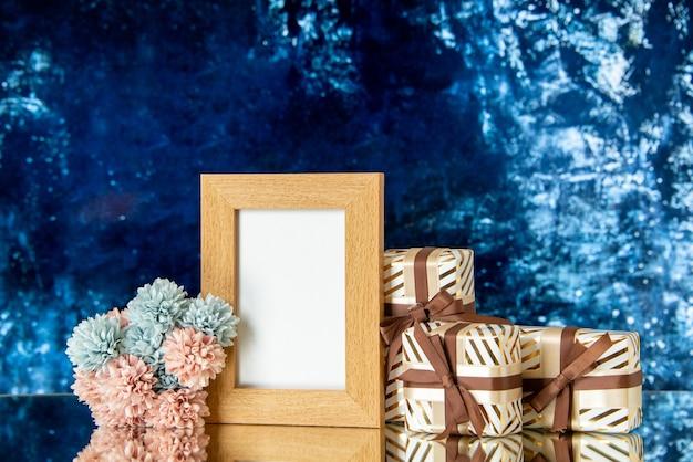 O feriado da moldura em branco de vista frontal apresenta flores em um fundo abstrato azul escuro