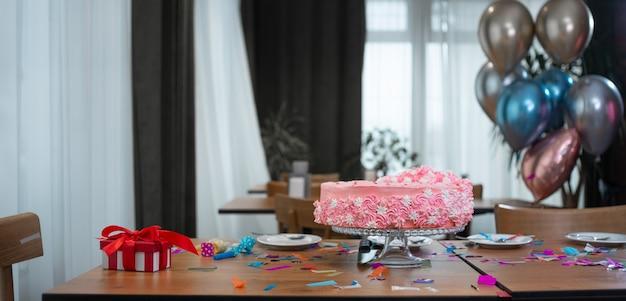 O feriado das crianças na mesa é um bolo de aniversário rosa, uma caixa vermelha com um arco e balões.