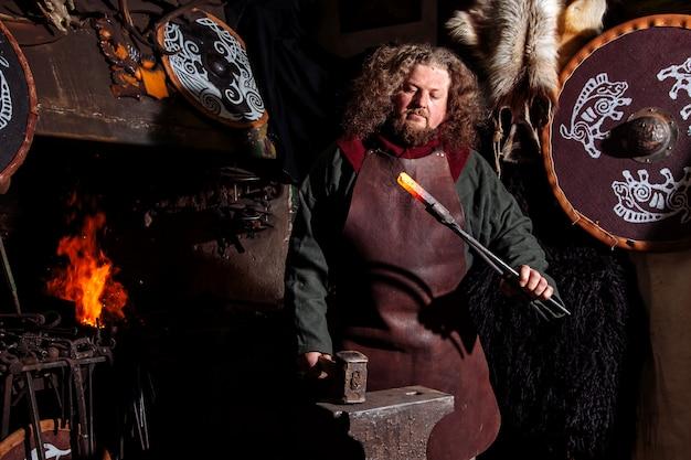 O ferreiro de viking forja armas na antiga forja vintage.