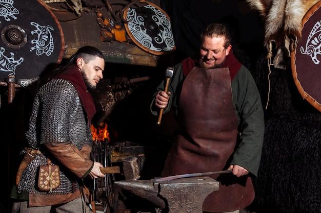 O ferreiro de vikings forja armas na forja velha do vintage.