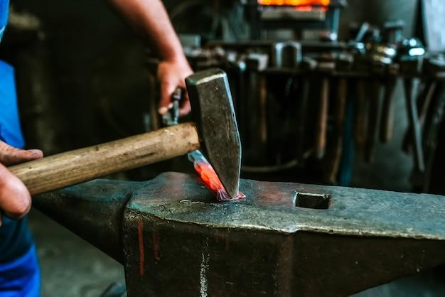 O ferreiro forjando manualmente o metal derretido na bigorna.
