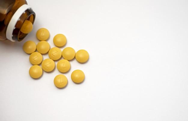 O ferro é um mineral muito valioso e um dos mais importantes em nosso corpo. vista frontal de um frasco marrom com vários comprimidos de ferro amarelo