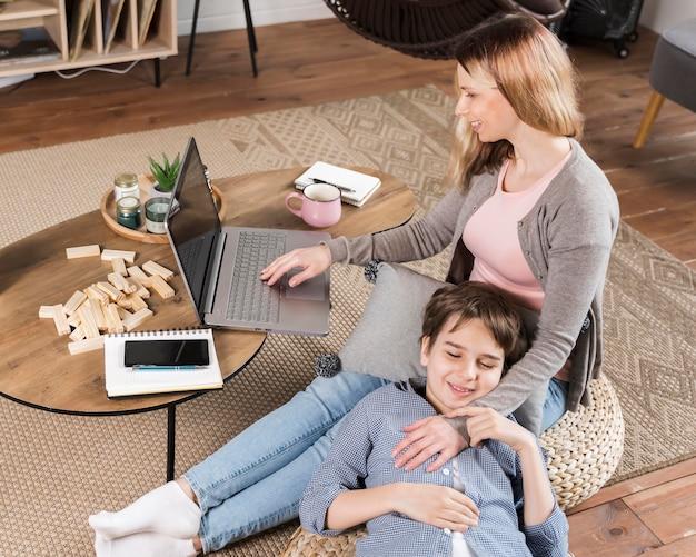 O filho adorável está feliz que a mãe está trabalhando em casa