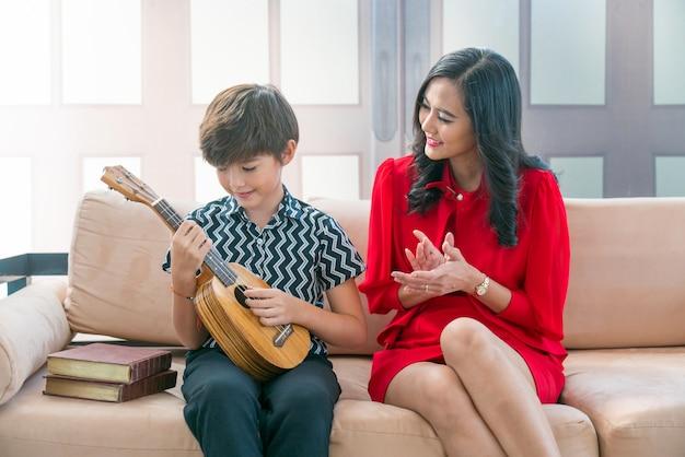 O filho asiático joga um quarteto de cordas havaiano com sua mãe na casa.