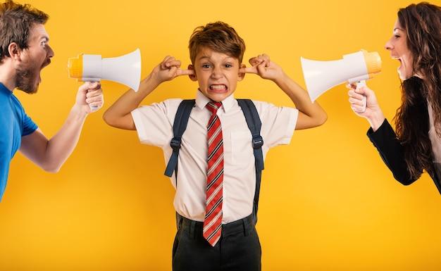 O filho do aluno cobre os ouvidos porque não quer ouvir a reprovação dos pais