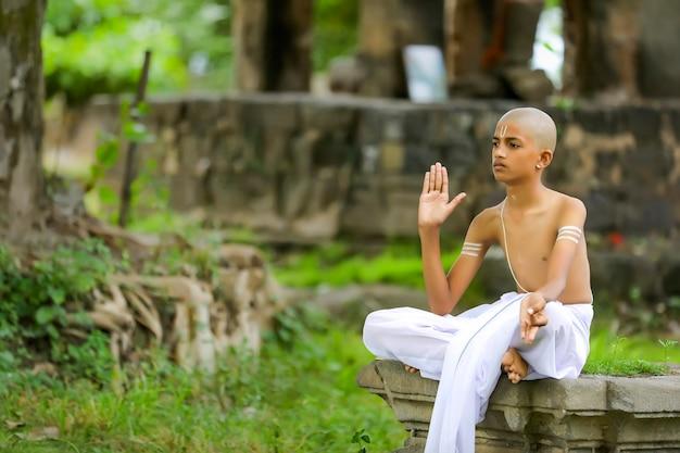 O filho do padre indiano fazendo meditação