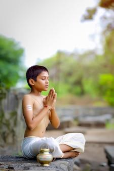 O filho do padre indiano fazendo meditação Foto Premium