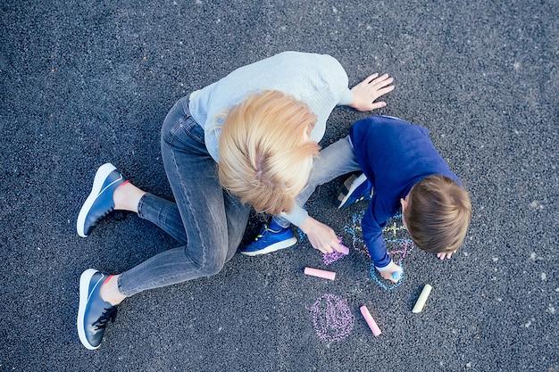 O filho e a mãe do bebê fofo pintaram com giz de cera colorido no asfalto do parque em um plano de fundo acima da vista