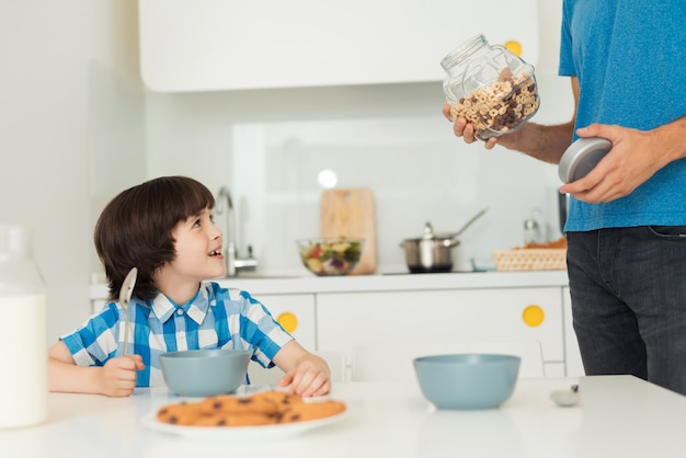 O filho e o pai de sorriso tomam o café da manhã na cozinha.