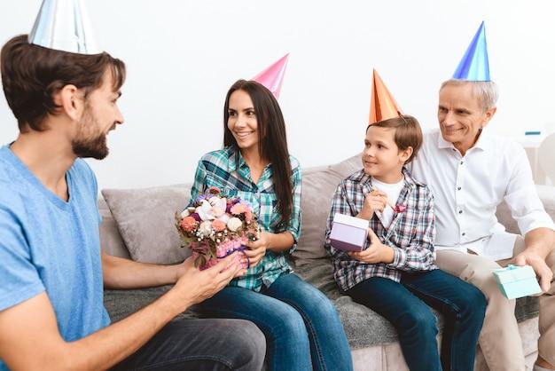 O filho e o sogro felicitam a mãe no aniversário.