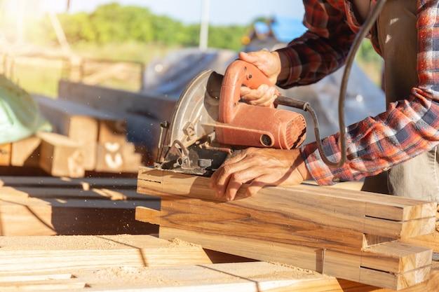 O fim acima da mão do carpinteiro que mói pranchas de madeira, trabalho na serra cortou a madeira.