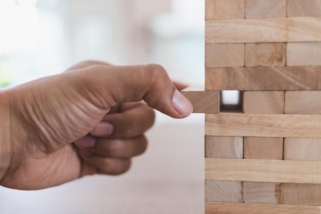 O fim acima da mão esquerda do homem toma a vara de madeira fora da torre de madeira (jenga). vista do lado