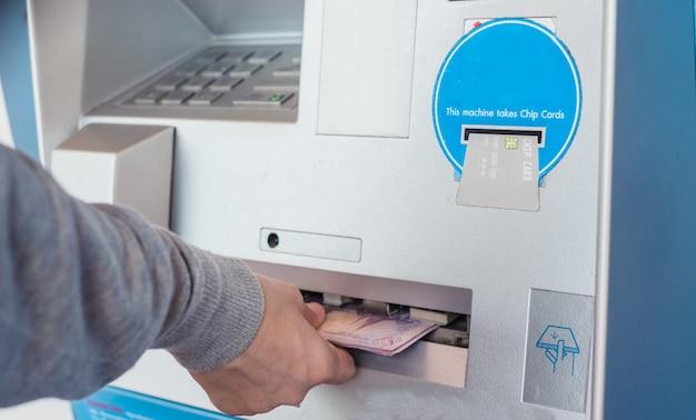 O fim da mão retira o dinheiro na moeda do baht tailandês da máquina do banco. sacar dinheiro em um caixa eletrônico.