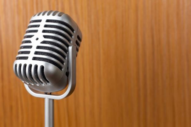 O fim do microfone do vintage acima da imagem no fundo de madeira.