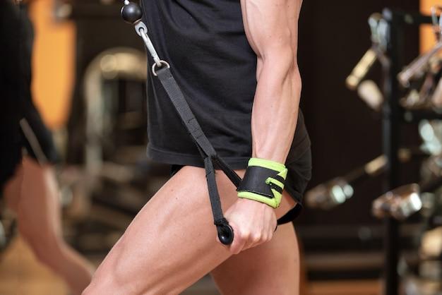 O fim muscular do homem do ajuste dos jovens que faz acima o tríceps puxa abaixo do exercício da extensão da corda no fitness center moderno.