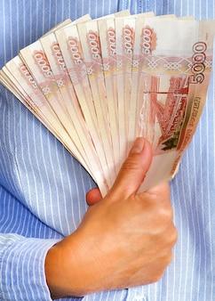 O financista segura um maço de notas na mão oferecendo empréstimos a juros e parcelados