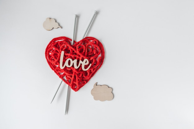 O fio para confecção de malhas vermelho com agulhas e sinal de madeira ama no fundo branco.